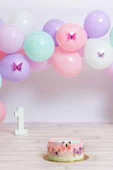 Fantastische kleurrijke verjaardagstaart met pastelkleurige ballonnen baby's eerste jaar verjaardagsideeën verticaal