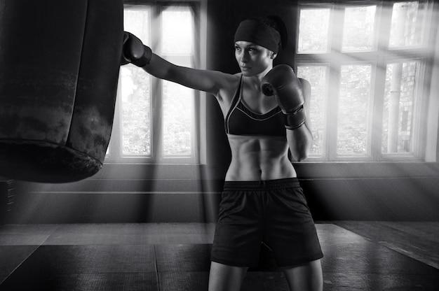 Fantastische sportvrouw boksen in een sportschool met een tas