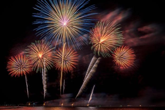 Fantastische veelkleurige vuurwerkviering van de grote boot over het overzees, vieringsconcept