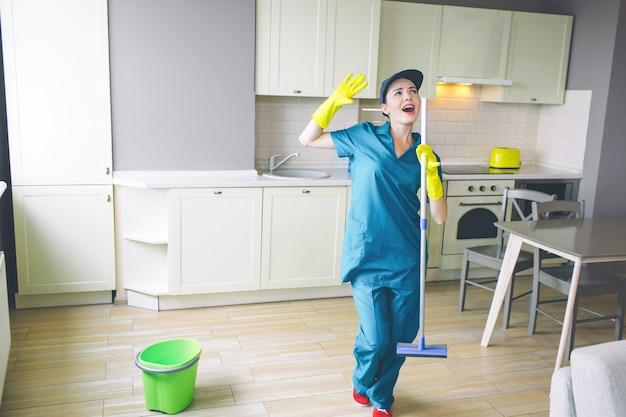 Fantastische vrouw staat in de keuken en houdt dweil in handen