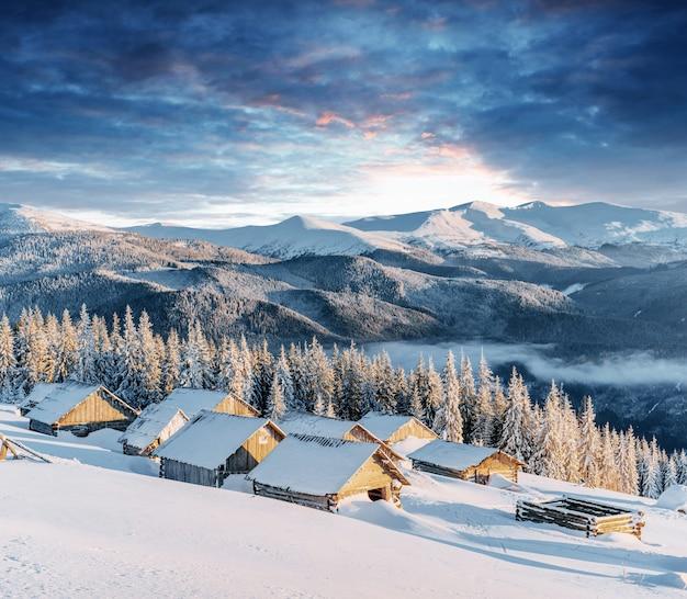 Fantastische zonsondergang over besneeuwde bergen en houten chalets