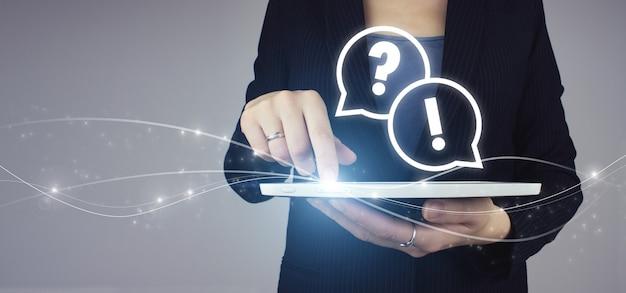 Faq veelgestelde vragen concept. witte tablet in zakenvrouw hand met digitale hologram faq vraag antwoord teken op grijze achtergrond. vragen online