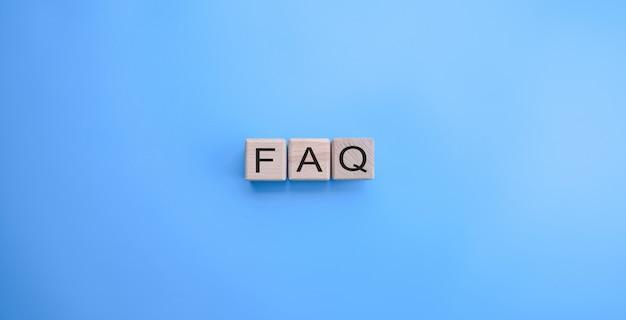 Faq-woord op de houten kubussen op blauwe achtergrond