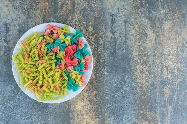 Farfalle en fusilli pasta op de plaat, op het marmeren oppervlak.
