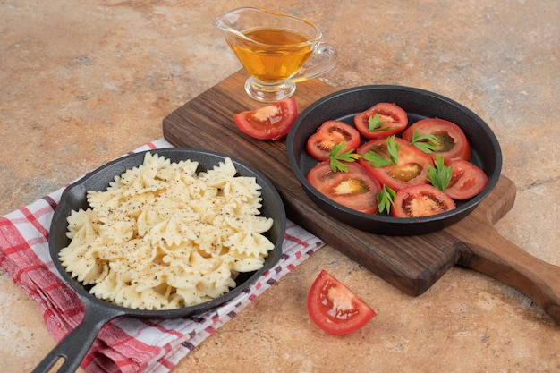 Farfalle en plakjes tomaat op zwarte pan met olie. hoge kwaliteit illustratie