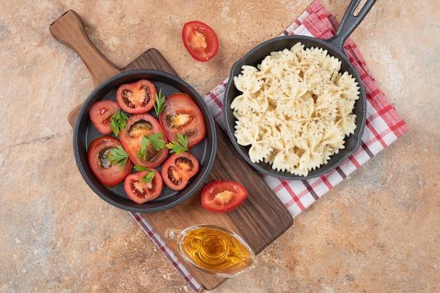 Farfalle en plakjes tomaat op zwarte pan met olie.