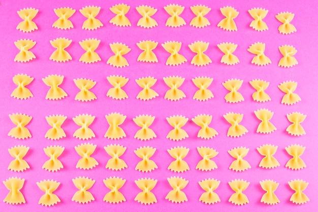 Farfalle gerangschikt in kolommen op een felroze achtergrond. pasta patroon.