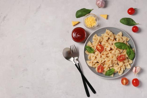 Farfalle pasta met cherrytomaatjes, tomatensaus en basilicum op witte achtergrond,