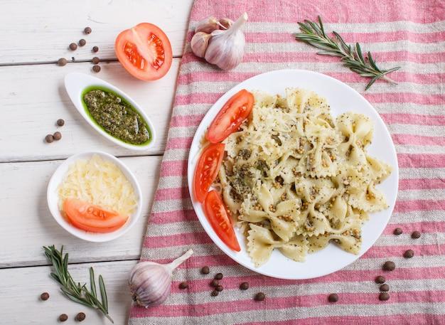 Farfalle pasta met pestosaus, tomaten en kaas op een linnen tafellaken op witte houten achtergrond.