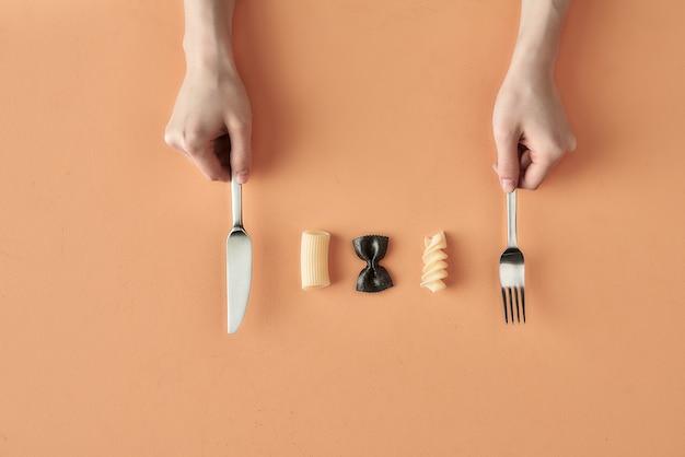 Farfalle, tortiglioni en fusilli pasta en handen met vork en mes