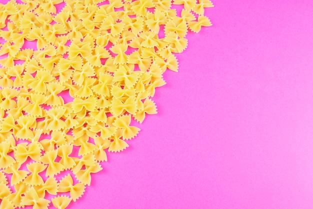 Farfalle verspreid in de hoek op een felroze achtergrond. pasta patroon.