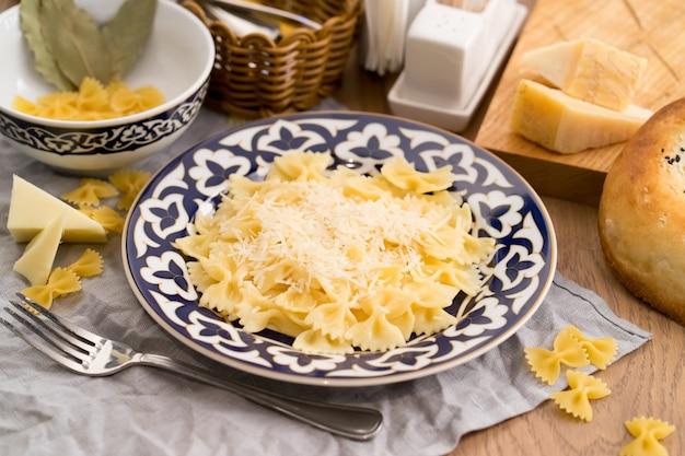 Farfalledeegwaren met kaas in een plaat met traditioneel oezbeeks
