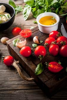 Farm rauwe biologische producten. voorbereiding van het diner in de italiaanse stijl. ingrediënten voor caprese salade, pasta, pizza. basilicum, tomaten, mozzarellakaas, olijfolie op een oude houten tafel.