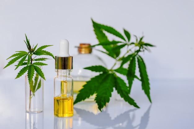 Farmaceutische cbd-olie en cannabistinctuur op een wit laboratoriumbureau. het concept van medische marihuana en alternatieve geneeskunde