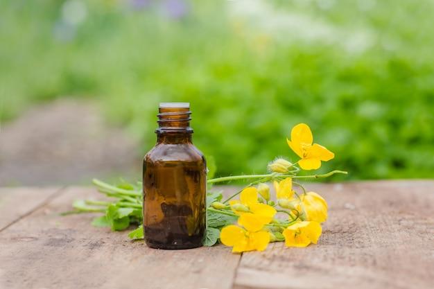 Farmaceutische fles met medicijnen van gele bloemen van chelidonium majus