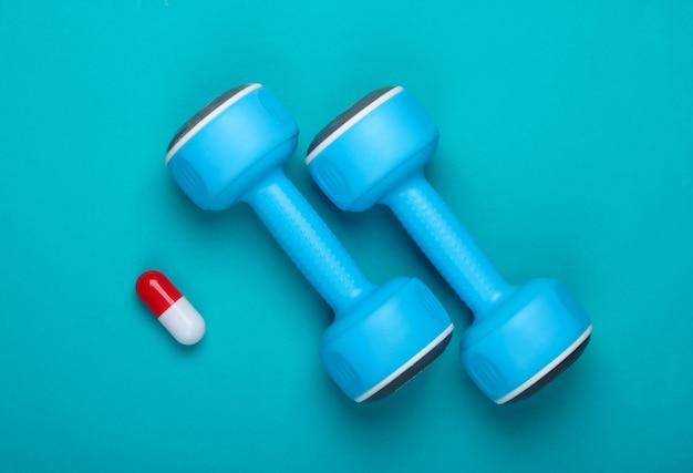 Farmacologie in de sport. halter en capsule op blauwe achtergrond. vitaminen, steroïden. bovenaanzicht