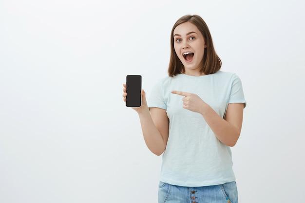 Fascineerde knappe jonge vriendelijke vrouwelijke winkelbediende in casual shirt met smartphone-scherm en wijzend op gadget praten over nieuwe functies en cool design, glimlachend poseren over grijze muur