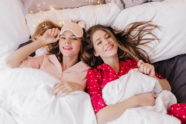 Fascinerend donkerbruin meisje dat met haar lange haar speelt terwijl ze naast haar zus ligt. overhead portret van lieve dames die in de ochtend ontspannen.