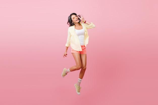 Fascinerend hipstermeisje in gele outfit tijd doorbrengen. romantische spaanse dame in stijlvolle sneakers dansen met plezier.