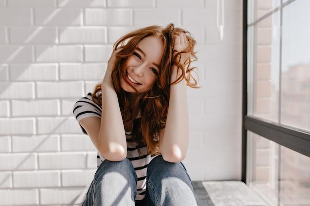 Fascinerend jong kaukasisch model dat thuis stelt. prachtig gembermeisje dat met haar haar speelt en lacht.