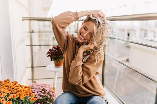 Fascinerend kaukasisch meisje dat bij terras glimlacht. portret van schattige blonde dame heeft een goede tijd in het weekend.