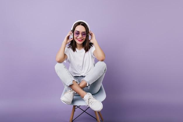 Fascinerend kaukasisch meisje wat betreft haar koptelefoon tijdens het poseren. binnen schot van lachen prachtige vrouw zittend op een stoel en muziek luisteren.