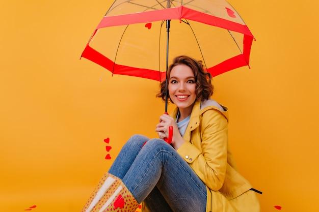 Fascinerend krullend meisje in rubberen schoenen poseren met plezier onder paraplu. binnenportret van lieve vrouw in de herfstuitrusting die op gele muur met glimlach wordt geïsoleerd.