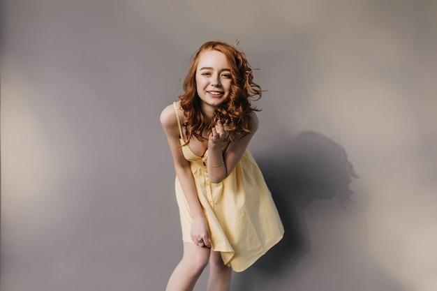 Fascinerend krullend meisje in trendy gele jurk lachen. gember jongedame plezier tijdens fotoshoot.