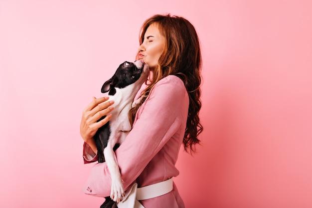 Fascinerend krullend meisje kussen franse bulldog. portret van blithesome europese vrouw liefde uitdrukken voor haar hond.