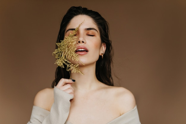 Fascinerend meisje dat groen blad houdt en met gesloten ogen staat. modieuze ontspannen vrouw die binnen fotoshoot geniet.