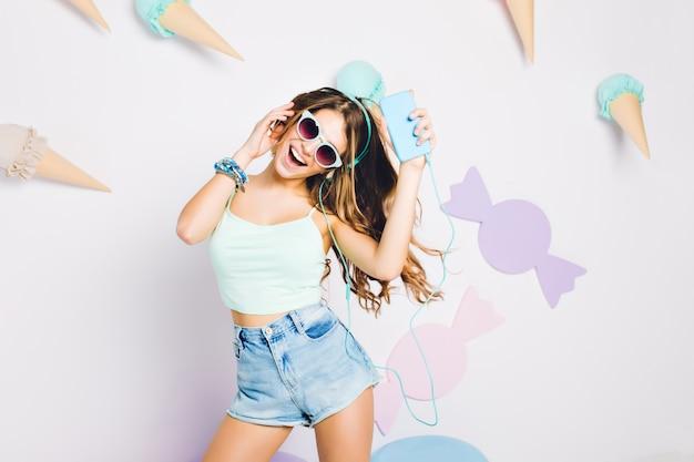 Fascinerend meisje in zwarte zonnebril en blauwe armband zingen en dansen op versierde muur. portret van zalige jonge vrouw in oortelefoons genieten van vrije tijd voor muur met snoep.