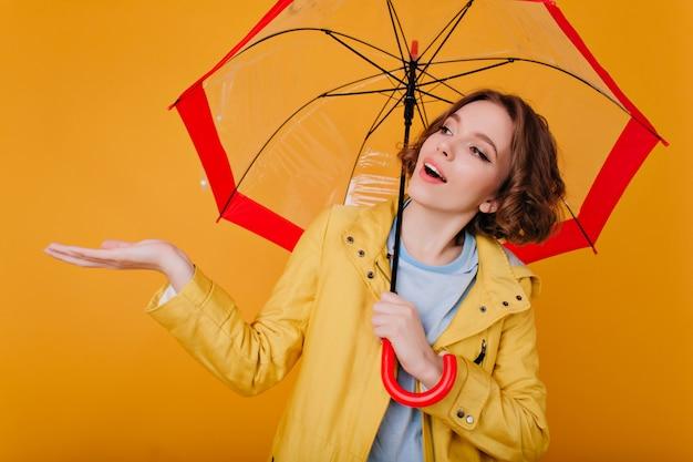 Fascinerend meisje met donker haar dat op regen wacht. studio portret van romantische jonge vrouw in herfst jas geïsoleerd op gele muur.