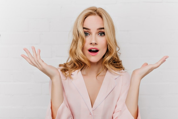 Fascinerend meisje met grote blauwe ogen die verbazing uitdrukken en zwaaiende handen geïsoleerd op een witte muur. mooie vrouw met krullend kapsel draagt roze pyjama poseren met verbaasd gezicht.