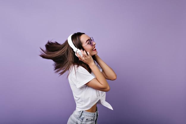 Fascinerend meisje met sluik glanzend haar dat danst en lacht. portret van grappige jonge vrouw in geïsoleerde hoofdtelefoon.