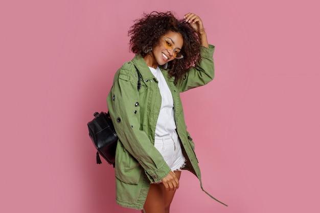 Fascinerend mix race model in trendy groene jas poseren op roze achtergrond. gele zonnebril, zwarte rugzak.