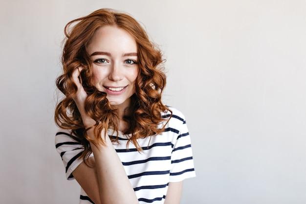 Fascinerend mooi meisje met gemberhaar dat positieve emoties uitdrukt tijdens fotoshoot. lief roodharig vrouwelijk model in vrijetijdskleding status.