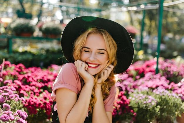 Fascinerend vrouwelijk model met krullend kapsel dat in tuin lacht. lieve blanke vrouw die oprechte emoties uitdrukt tijdens het poseren met bloemen.