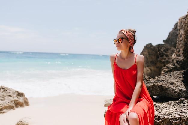 Fascinerend wit vrouwelijk model dat door een zonnebril geniet van uitzicht op de oceaan. buiten foto van ontspannen jonge dame in rode jurk poseren op rots in de buurt van zee.