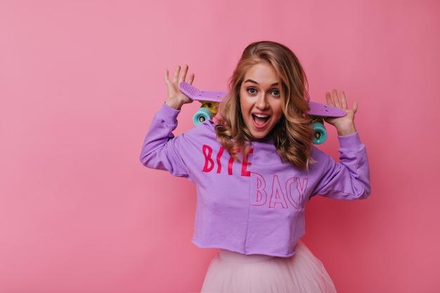 Fascinerende blanke vrouw in trendy shirt met roze skateboard. leuk blonde vrouwelijk model dat van vrije tijd geniet.