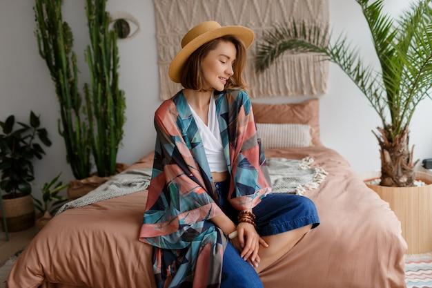 Fascinerende brunette vrouw in strooien hoed chillen thuis in gezellige boho interieur