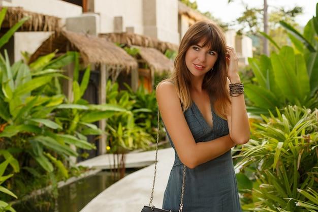 Fascinerende europese vrouw in zomerjurk wandelen in tropisch resort. groene tropische planten op achtergrond.