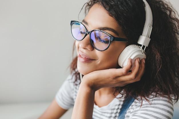 Fascinerende jonge vrouw met bruine huid en lange zwarte wimpers die geniet van favoriete muziek in grote oortelefoons