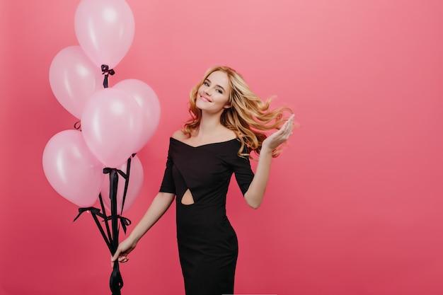 Fascinerende slanke vrouw speelt met krullend haar tijdens fotoshoot met feestballonnen. elegante feestvarken in zwarte jurk genieten van evenement en poseren op roze muur.