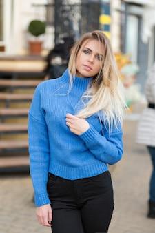 Fascinerende stijlvolle dame met lang blond haar en blauwe ogen poseren voor de camera tijdens het buiten lopen
