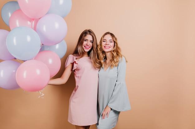 Fascinerende verjaardagsvrouw in roze outfit die van feest geniet