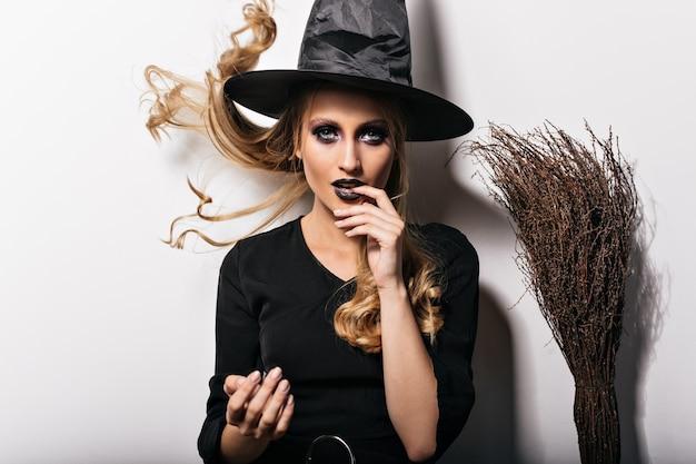 Fascinerende vrouw die met zwarte make-up van carnaval geniet. foto van modieus blond meisje in halloween kostuum.
