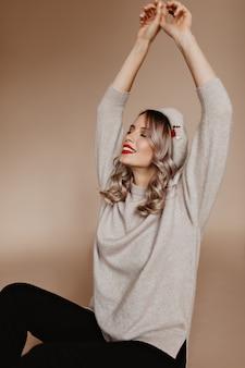 Fascinerende vrouw in bruine trui poseren met handen omhoog