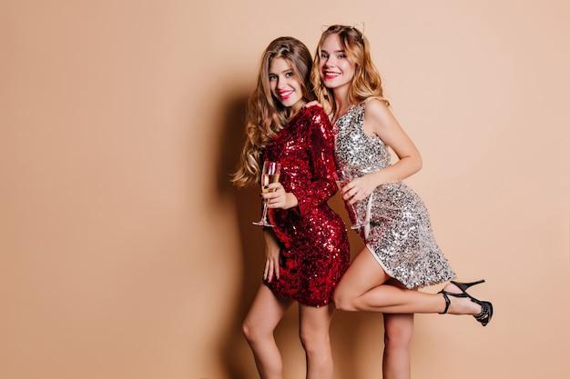 Fascinerende vrouw in rode jurk met lange mouwen met glas champagne op verjaardagsfeestje