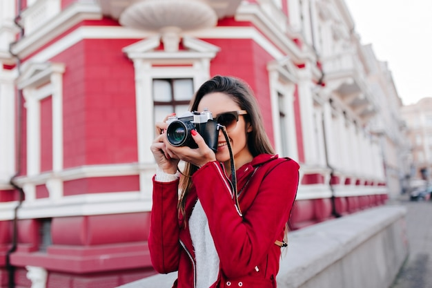 Fascinerende vrouwelijke fotograaf die in de ochtend in de stad werkt