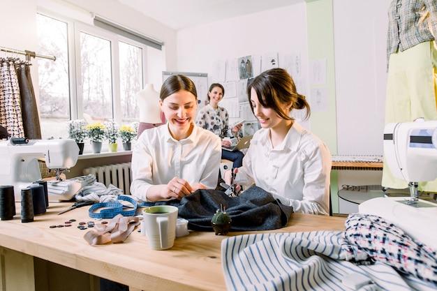 Fashion design mannequin meting concept. twee mooie dames naaisters knippen kledingdetails op de schetslijnen. lachende modeontwerper met laptop op de achtergrond